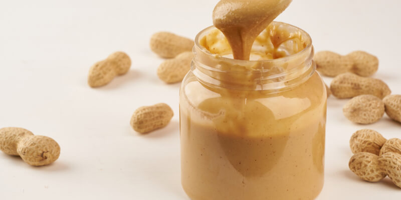 Jar-of-peanut-butter-and-peanuts-in-shell-on-a-white-table