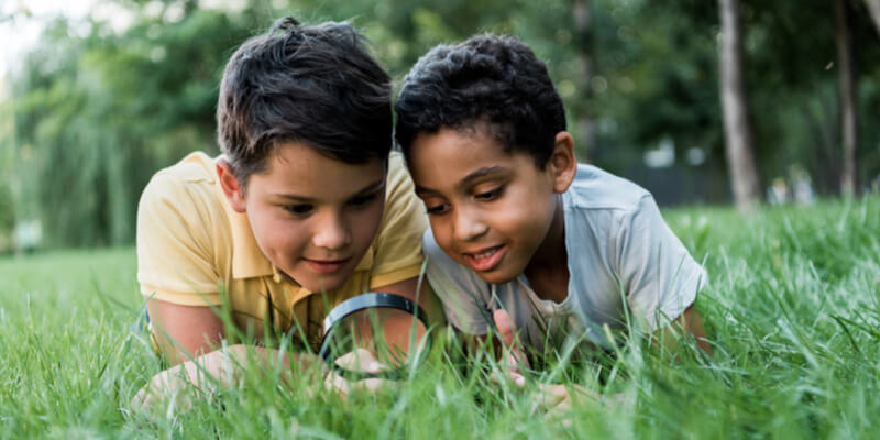 selective focus of multicultural boys lying on grass and looking through magnifier